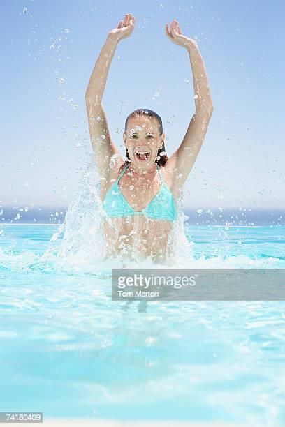 Woman in bikini splashing and smiling in pool
