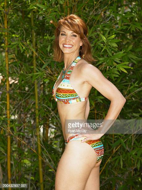 woman in bikini standing with hands on hips, portrait, side view - arms akimbo stock pictures, royalty-free photos & images