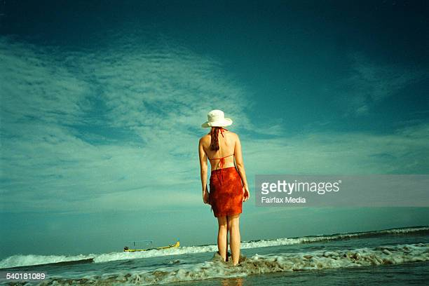 A woman in bikini stands on the shoreline of a tropical beach 23 April 2002 AFR Picture by GREG NEWINGTON