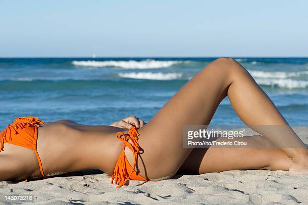 Woman in bikini sunbathing on beach, mid section
