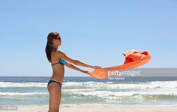 Mujer en bikini en la playa con toalla de playa