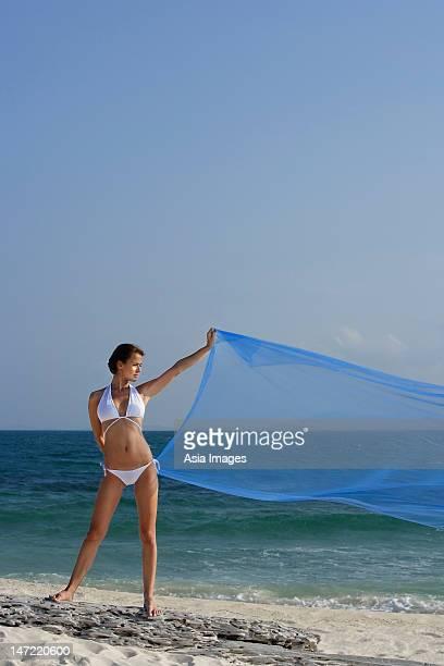 woman in bikini with flowing blue fabric