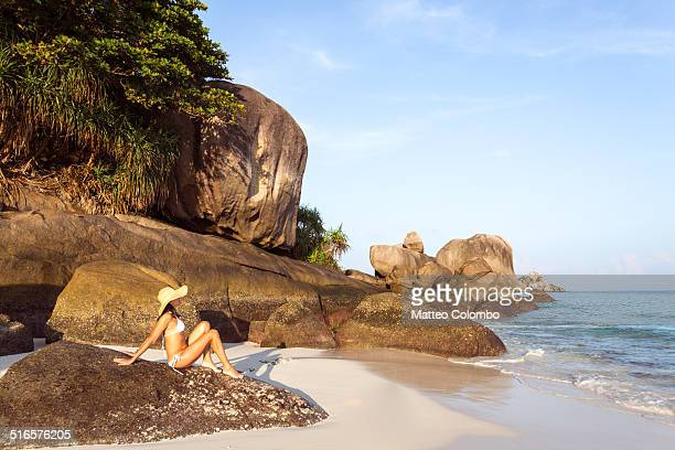 Woman in bikini with hat sitting on tropical beach