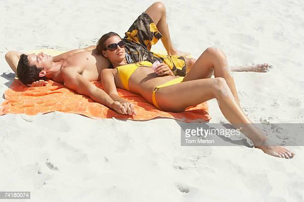 Woman in bikini with MP3 player lying down on man