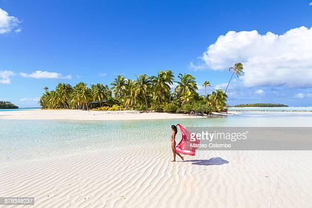Woman in bikini with sarong walking near island