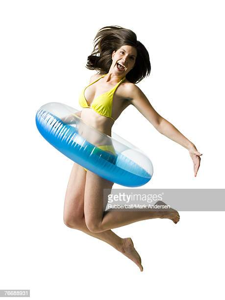 Woman in bikini with swimming ring around waist jumping and smiling