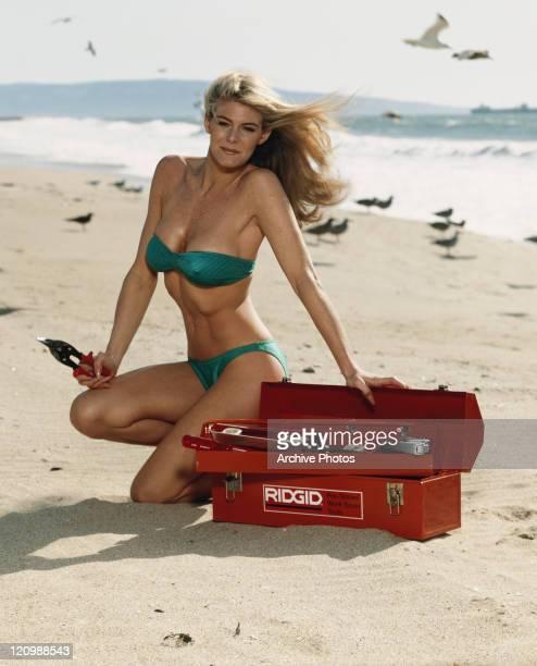 Woman in bikini with tool box on beach