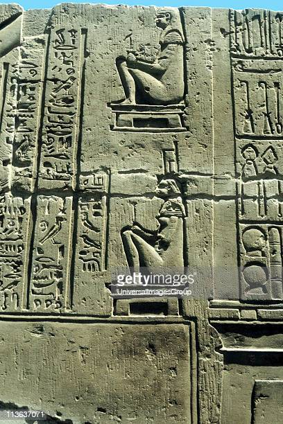 Woman in birthing chair various medical instruments on right Limestone relief Kawm Umbu