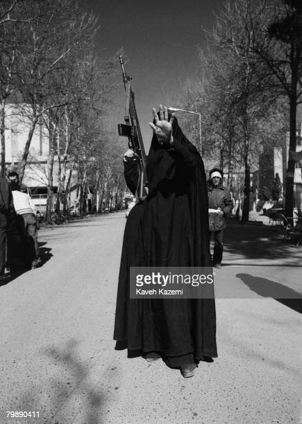 A woman in black chador and carrying a G3 machine gun holds up her hand in a gesture of defiance to the camera Tehran 12th February 1979 She is...