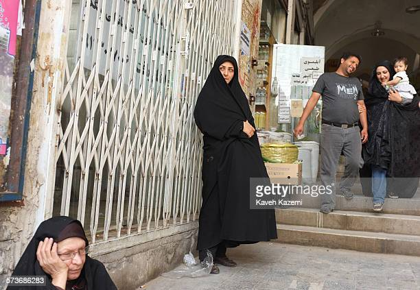 Woman in black chador stands at the entrance of the bazaar on 10th May 2012 in Kashan, Iran.