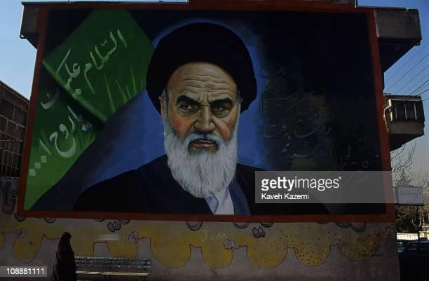 A woman in black chador walks past a bench under a large mural of Ayatollah Khomeini Tehran Iran April 1 1999