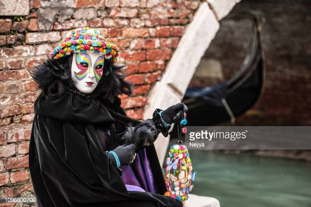 woman in black costume at venice carnival wearing beautiful venetian mask with colorful roses - mardi gras photos stock pictures, royalty-free photos & images
