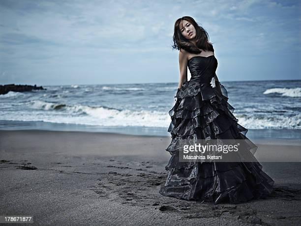 Woman in black dress at sea beach.