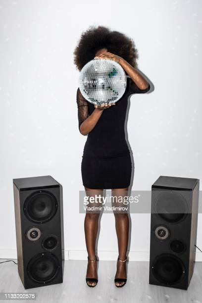 ディスコボールを保持し、隠す黒のドレスの女性 - funny black girl ストックフォトと画像