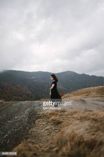 Woman in black dress in mountains