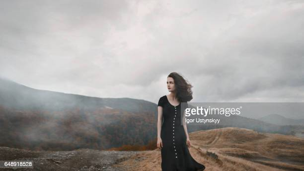 woman in black dress in mountains - black dress stock pictures, royalty-free photos & images