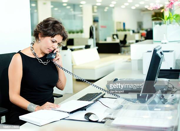 woman in black dress speaking on phone on office - secretary stock photos and pictures