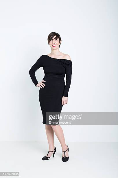 woman in black dress standing smiling