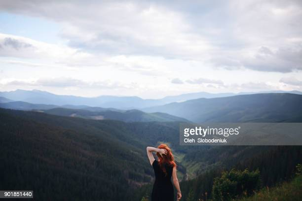 woman in black dress walking in the mountains and looking at view - power in nature stock pictures, royalty-free photos & images