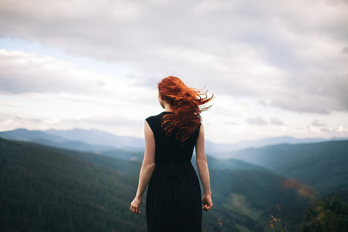 Woman in black dress walking in the mountains and looking at view 901851452