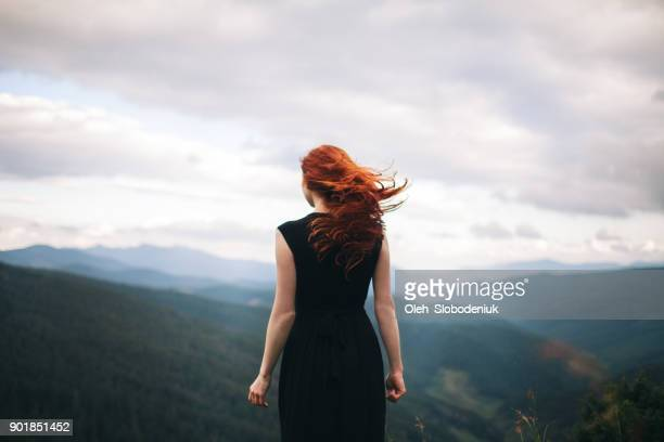 woman in black dress walking in the mountains and looking at view - vento foto e immagini stock