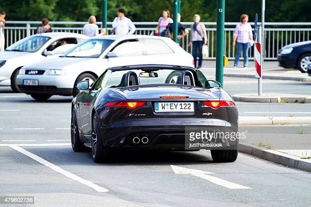 woman in black jaguar f type convertible - jaguar car stock pictures, royalty-free photos & images