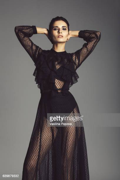 woman in black lace dress - women in see through dresses stock photos and pictures