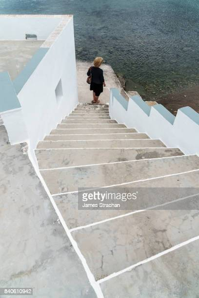 Woman in black looking out to sea at bottom of graphic white and grey steps, Heronissos Village, Sifnos, Cyclades Islands, Greece