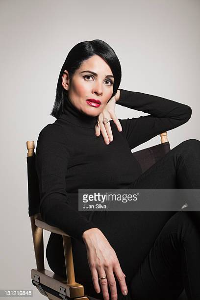 Woman in black sitting on black chair, portrait