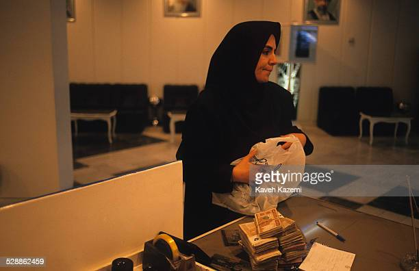 Woman in black veil deposits wads of banknotes brought in a plastic bag at the Tejarat Bank on Taleqani Avenue, Tehran, Iran, 11th December 1998.