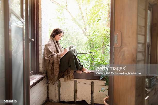 Woman in blanket writing on balcony