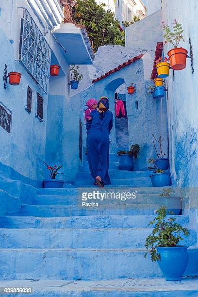 woman in blue djellaba and child in blue city, morocco - moroccan girls stock photos and pictures