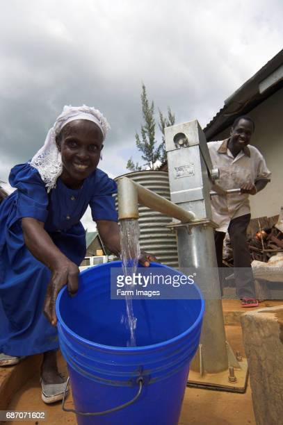 Woman in blue dress collecting water from new pump in village western Kenya Africa