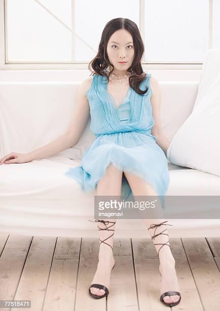 woman in blue dress sitting on sofa - スカート ストックフォトと画像