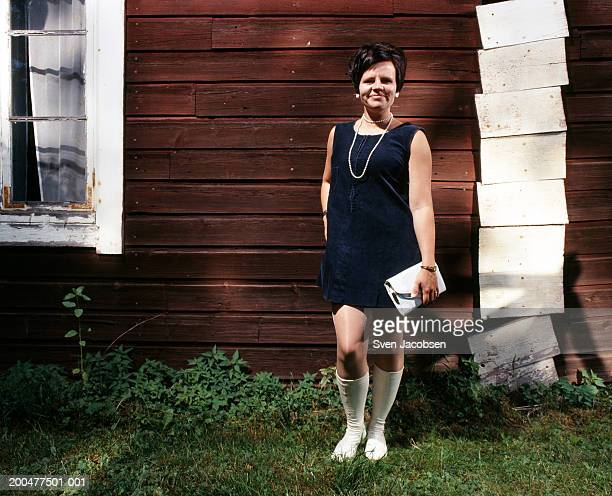 Woman in blue dress standing outdoors, smiling, portrait