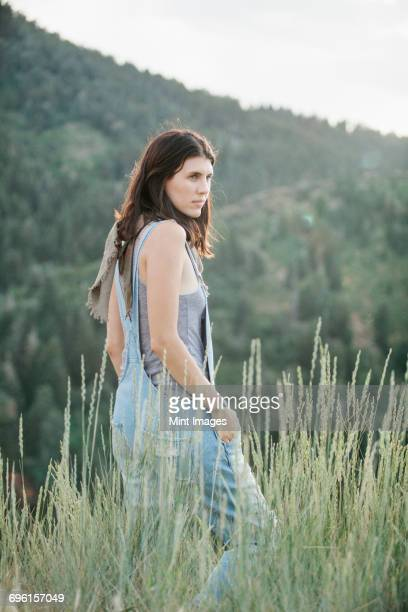 A woman in blue dungarees walking through long grass.