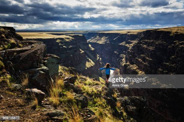Woman in blue jacket stands at brink of Bruneau Canyon with arms outstretched, southwestern Idaho