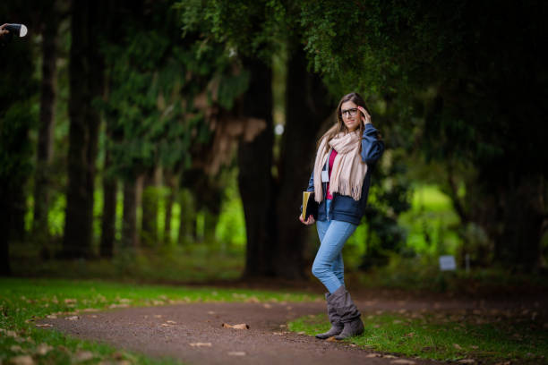 woman in blue jersey and blue jeans walking in a park with a book