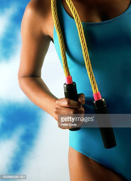 woman in blue swimsuit and holding jumping cord, mid section, close-up