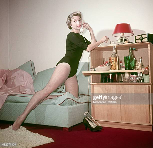 Woman in bodysuit and fishnet stockings posing leaning on a cocktail cabinet with a telephone in the hands. 1950s
