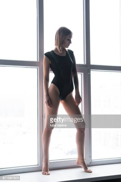 Woman in bodysuit at the window