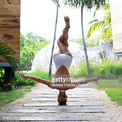 Woman In Bodysuit Performing Handstand With Legs Crossed At Knee