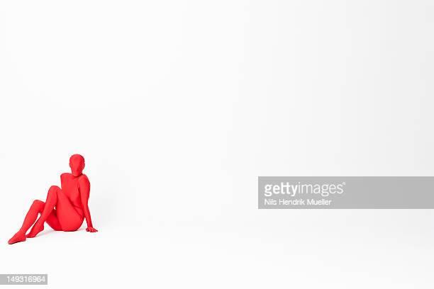 Woman in bodysuit sitting on floor
