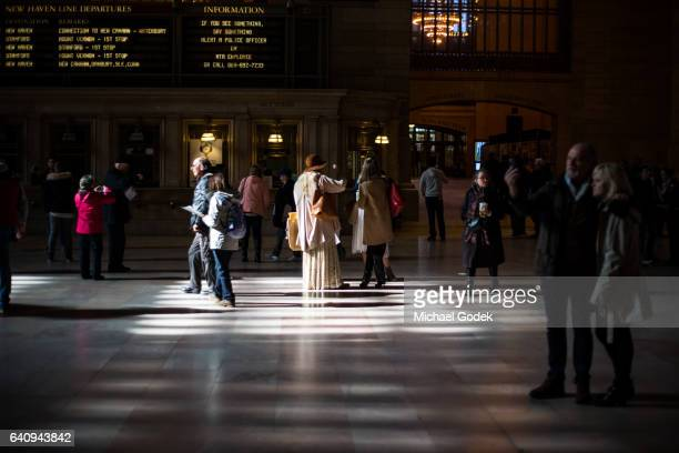 Woman in bohemian outfit standing in bright spotlight in the middle of Grand Central Station surrounded by people