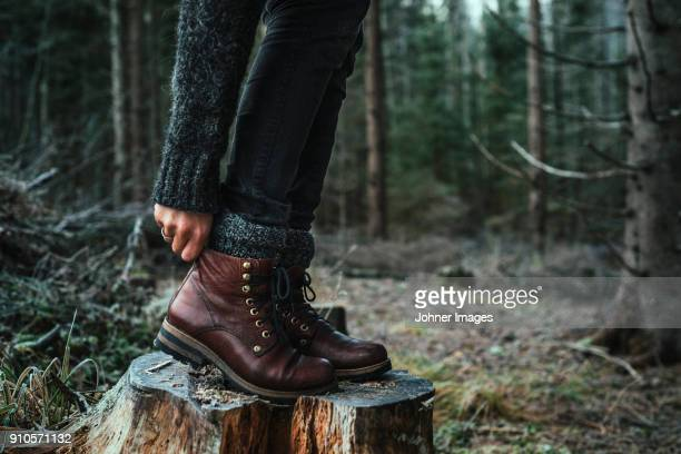 woman in boots standing on a stump - leather boot stock pictures, royalty-free photos & images