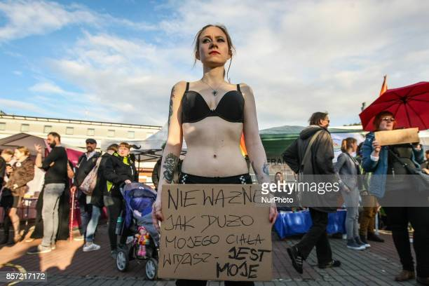 Woman in bra holding banner that speaks No matter how much my body you can see it's mine is seen in Gdansk Poland on 3 October 2017 Demonstration...