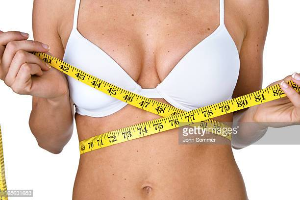 Woman in bra measuring herself
