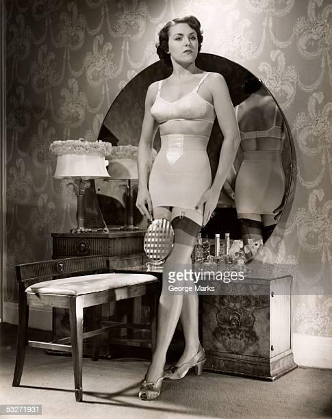 woman in brassiere and girdle at her mirror - girdle stock-fotos und bilder
