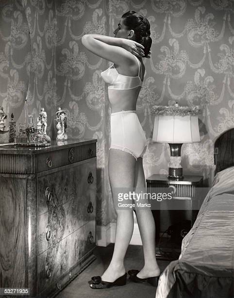 Woman in brassiere and panties in her bedroom