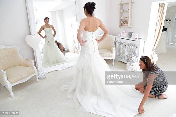 woman in bridal shop having a dress fitting. - wedding dress stock pictures, royalty-free photos & images